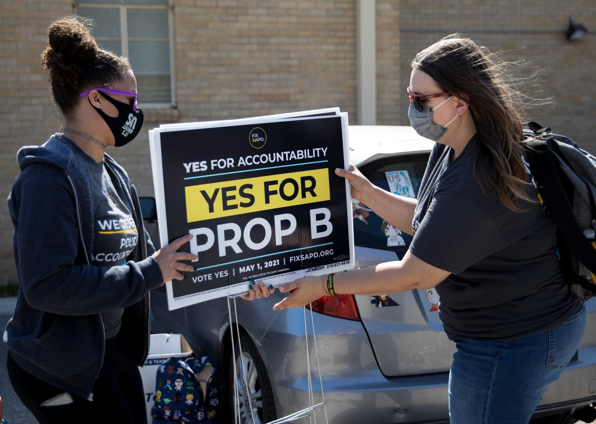 Ananda Tomas, left, deputy director of Fix SAPD, hands yard signs to Desiree Schanding before block walking to raise support for Proposition B on April 10.