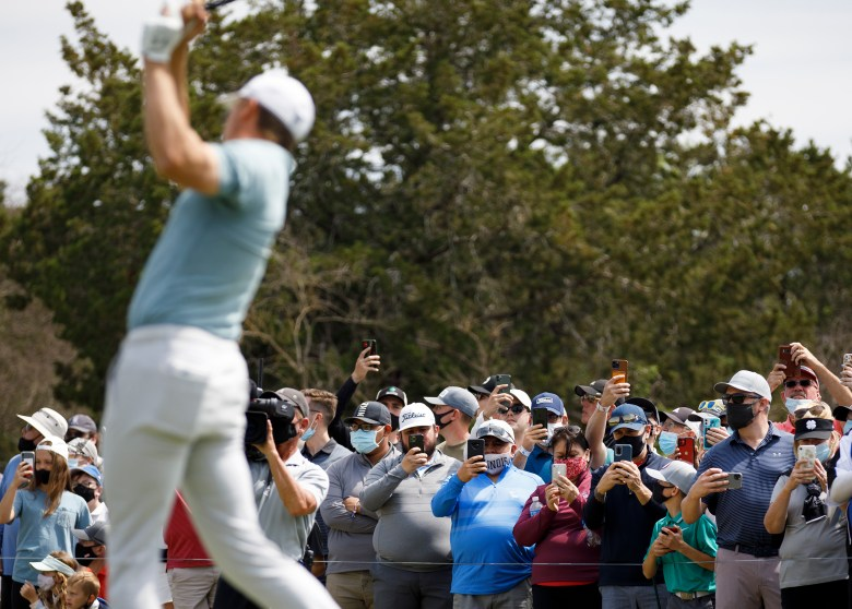 Spectators use their phones to capture Jordan Spieth as he hits a teeshot on the seventh hole during the Texas Open at TPC San Antonio on Friday.