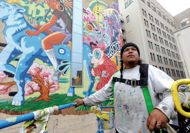 """Muralist Rudy Herrera poses for a portrait in front of his new mural titled """"The Last Parade"""" in downtown on Thursday."""