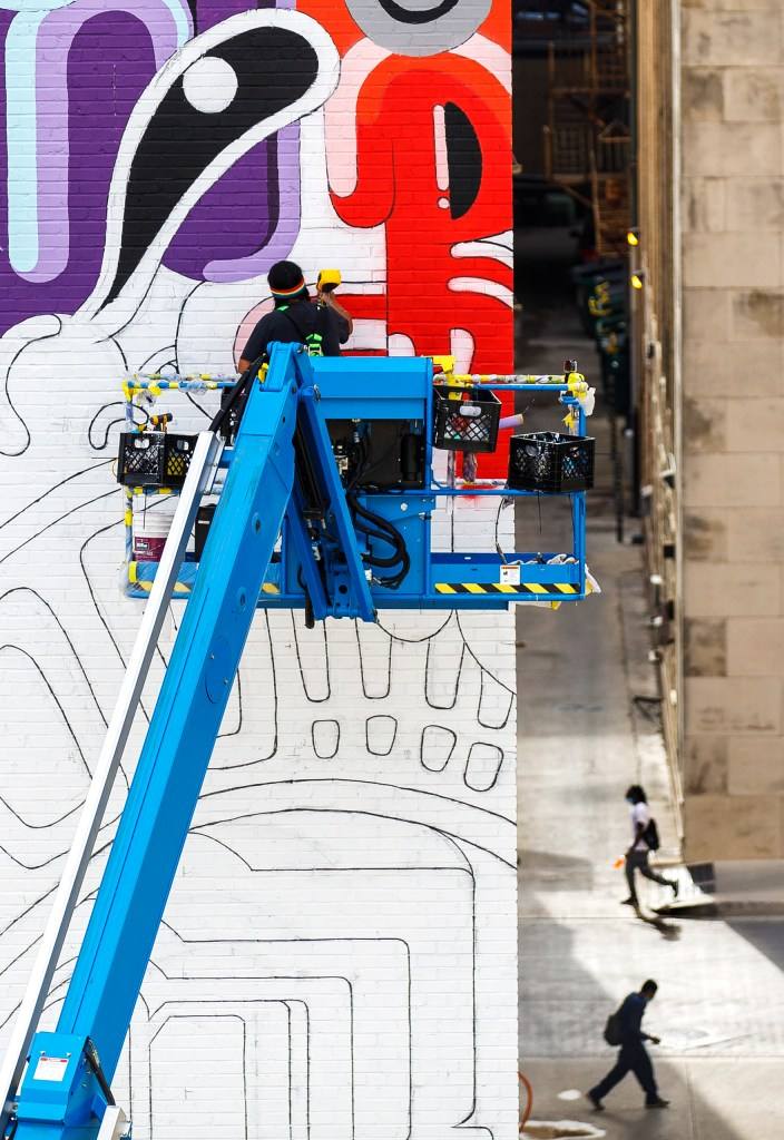 """Muralist Rudy Herrera works on a mural he's called """"The Last Parade"""" on the east side of the Kress building in downtown."""