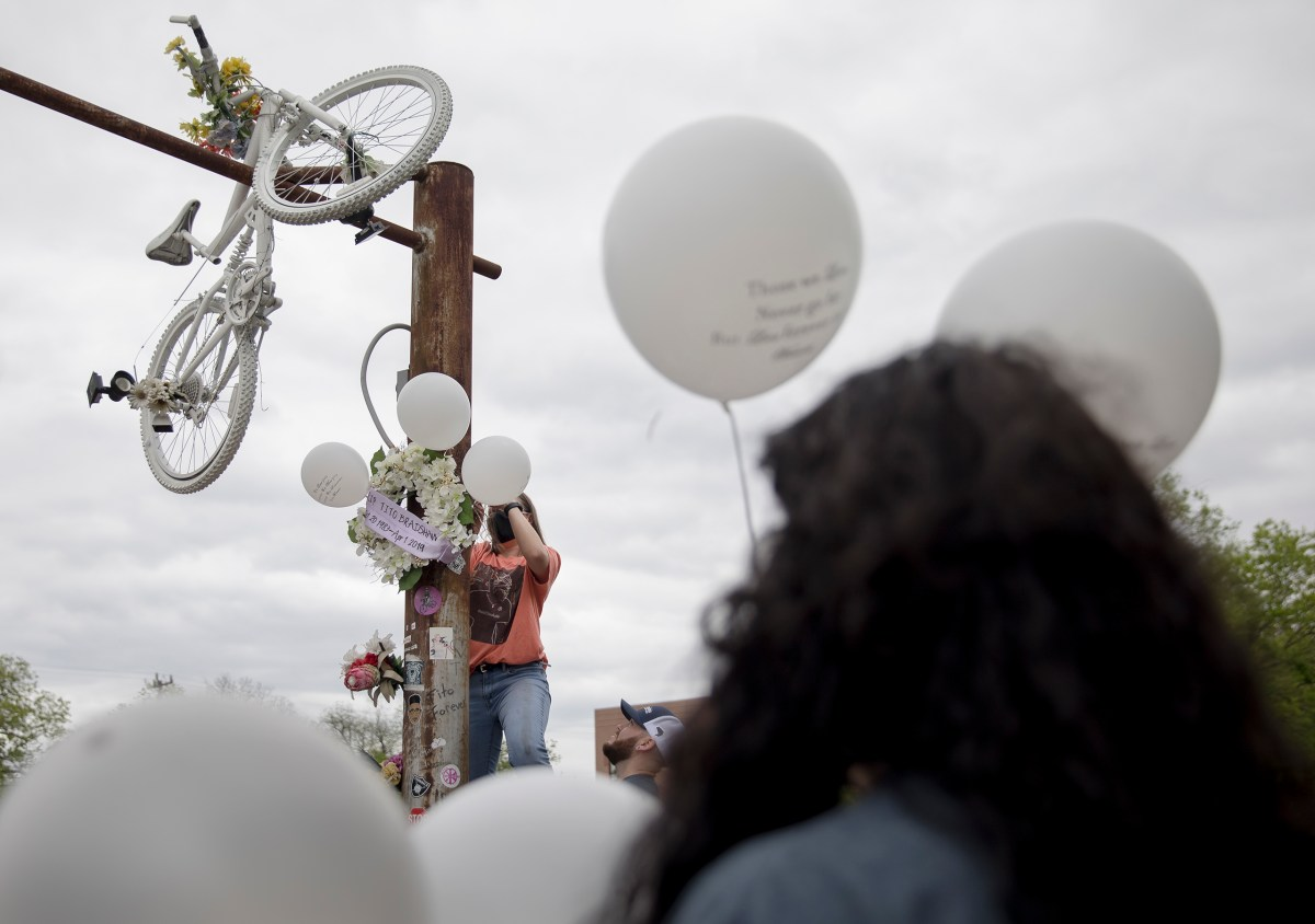 Encar Dinger hangs a wreath during an event honoring bicyclist Tito Bradshaw on Saturday. Bradshaw, a beloved local cyclist, was struck and killed by an alleged drunk driver on April 1, 2019, on East Houston Street. Family members and friends gathered to demand justice for Tito and urge city officials to approve a bike-safe infrastructure plan.