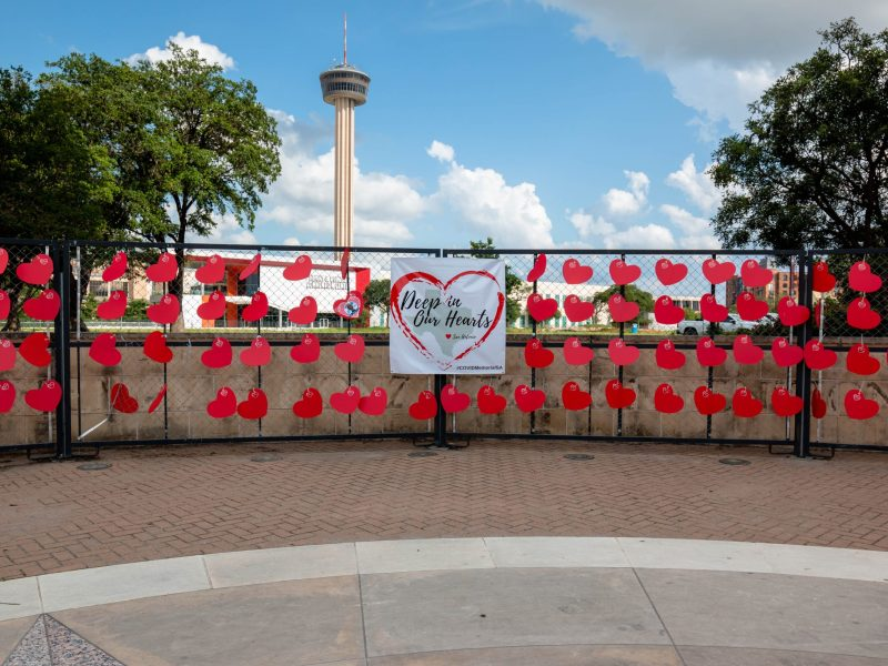 The Tower of the Americas stands tall in the distance as a memorial honors the nearly 3,500 lives lost to COVID-19 during the pandemic.