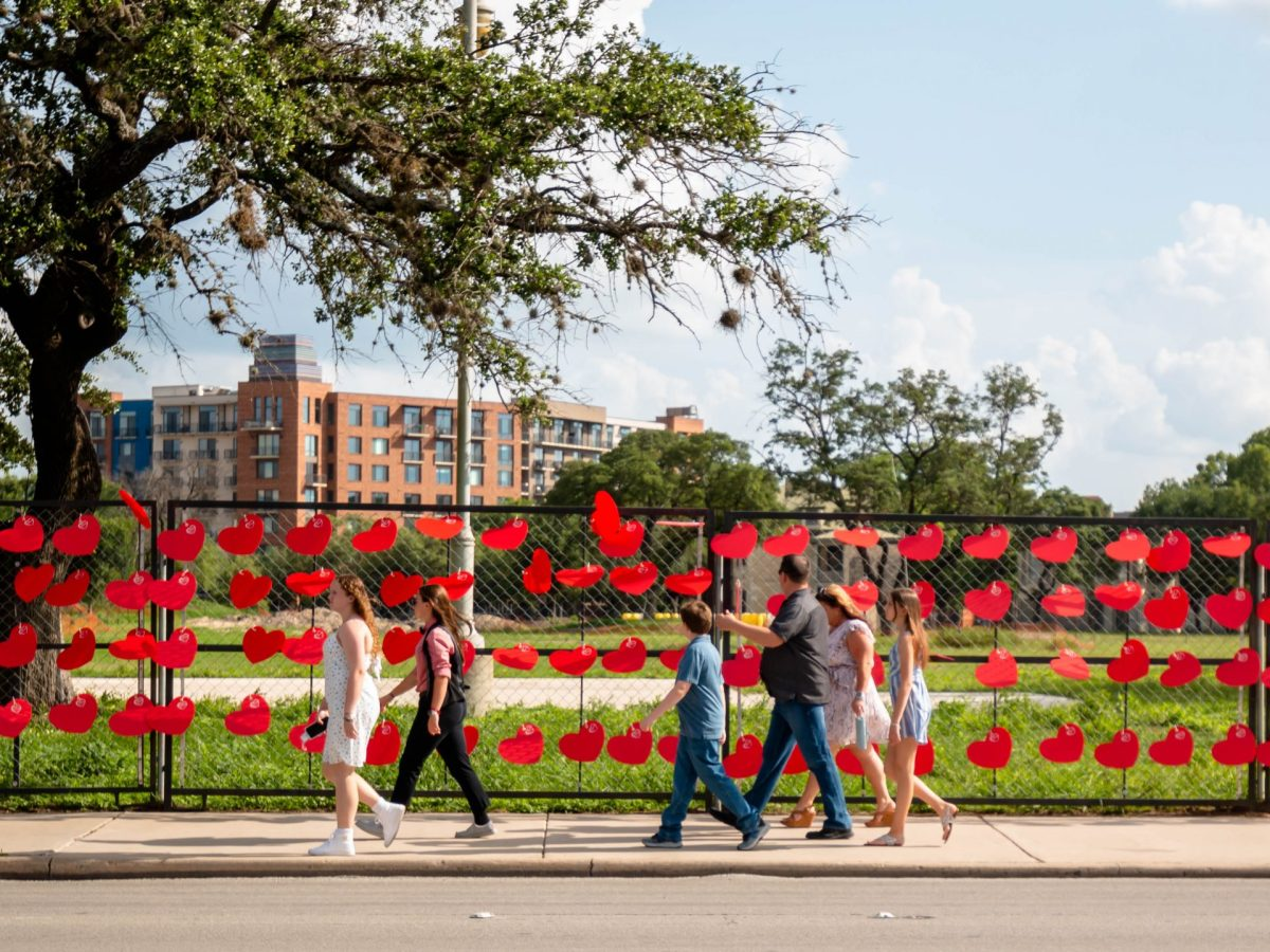 A family walks past the wall of red heart shapes along Market Street.