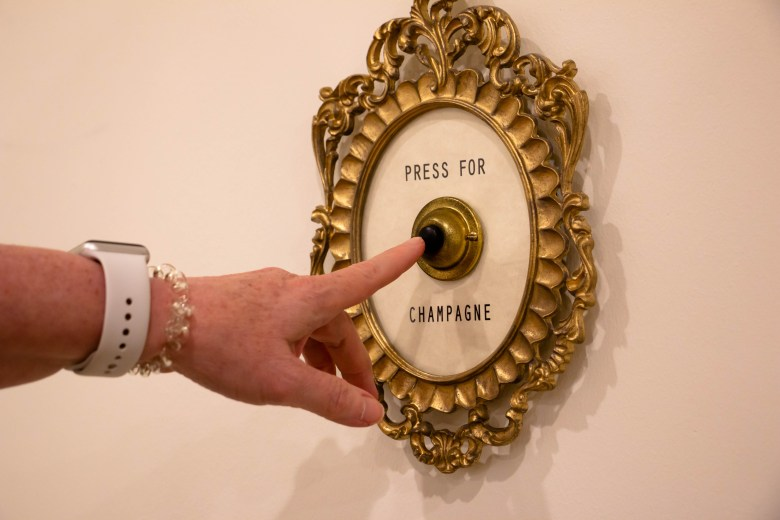 """A doorbell with a sign that reads """"Press for Champagne"""" is inside of the Bride's quarters in Estancia Del Norte."""