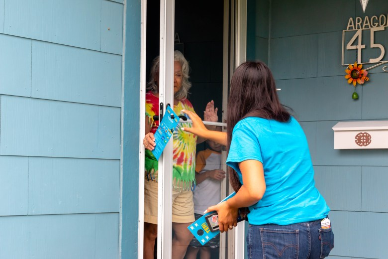 Teri Castillo hands an information leaflet about her campaign to Yolanda Aragon with her grandson, Eli, by her side. Castillo went canvassing at specific homes in District 5.