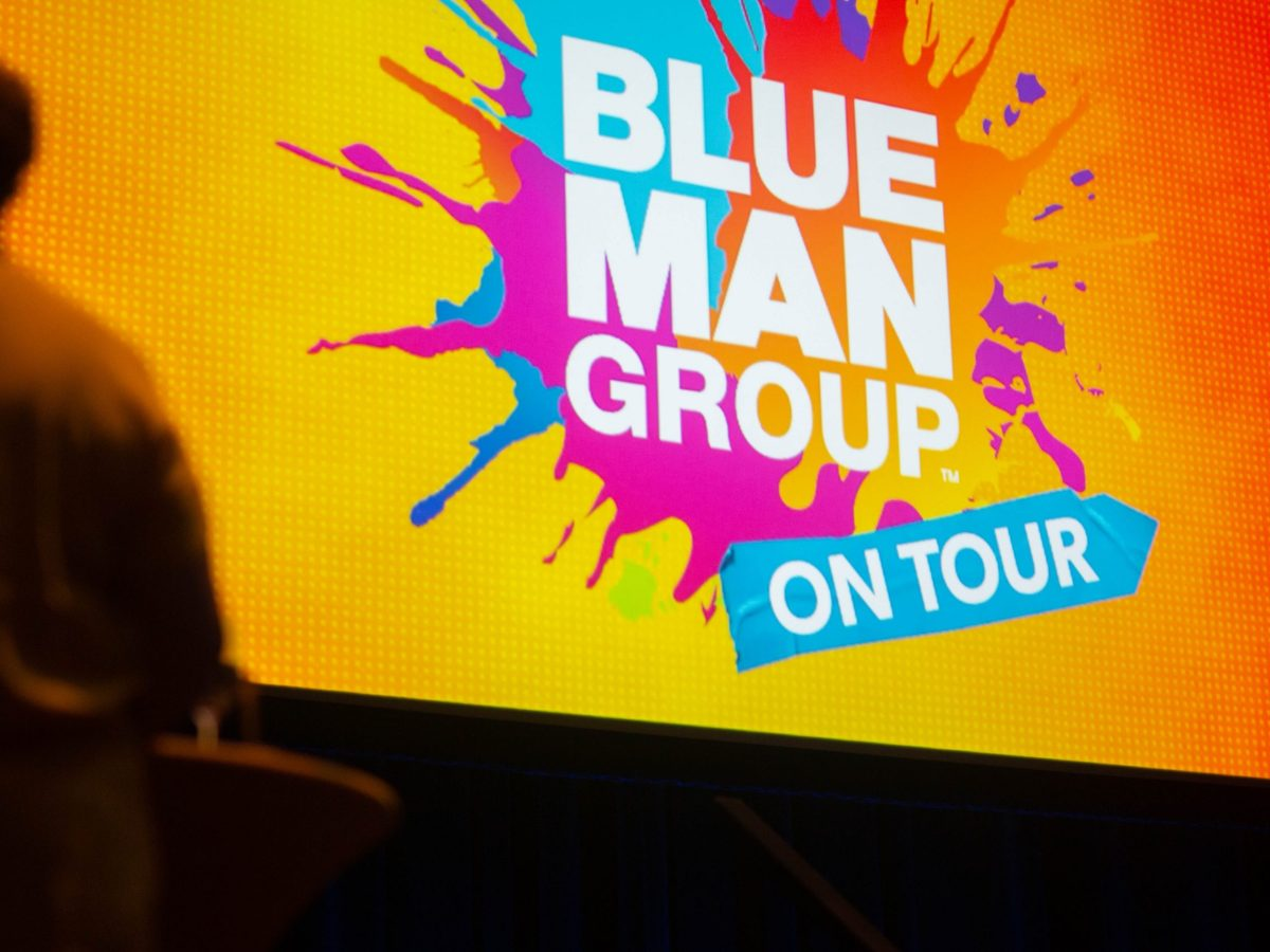 """A woman watches the giant screen as a video announces the signature series for the 2021-2022 season at the Tobin Center for the Performing Arts. Shows include the play """"An Officer and a Gentleman"""" and performances from the Blue Man Group."""