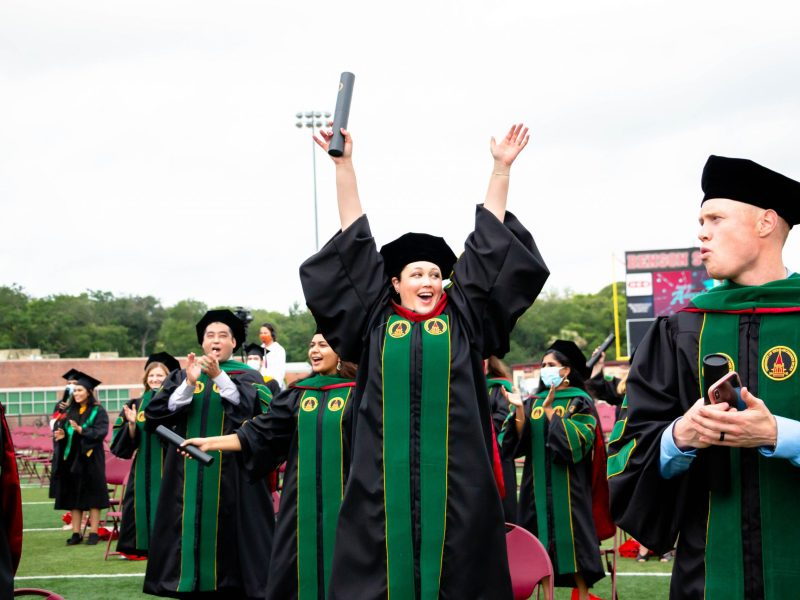 An OLLU graduate lifts her arms in celebration after the graduates were officially confirmed in their degrees.