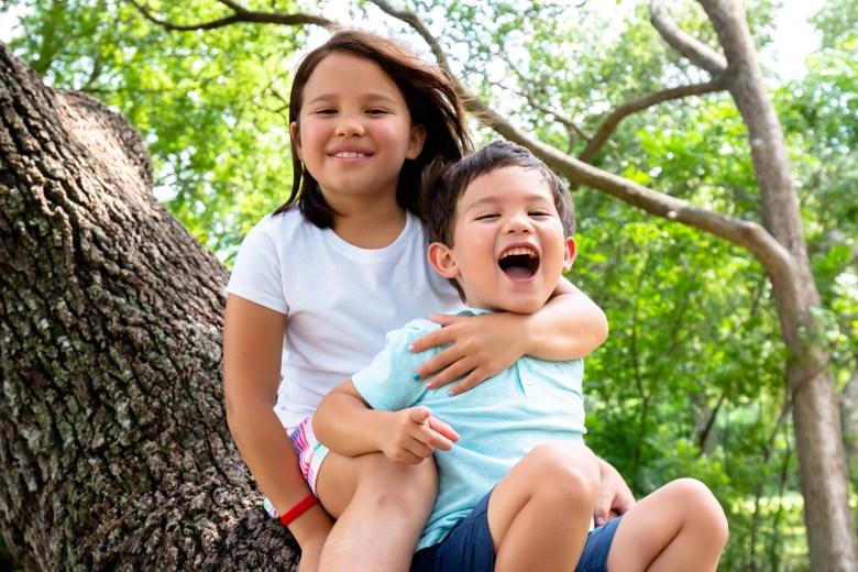 Elliot, 8, hugs het little brother, Finn, 4, on a big tree in the Heritage Oaks Park, which is run by the city of Schertz.