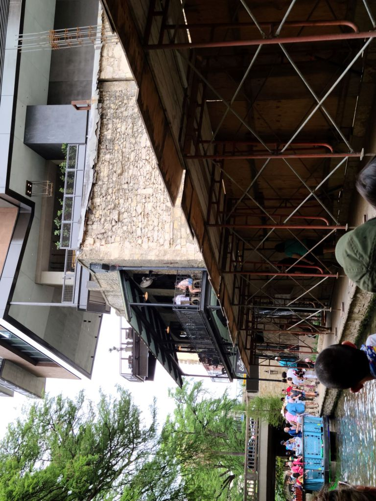 Passengers look up at the new Canopy by Hilton hotel, on the far side of the historic Esquire Tavern, while cruising along the San Antonio River Walk on May 9, 2021.