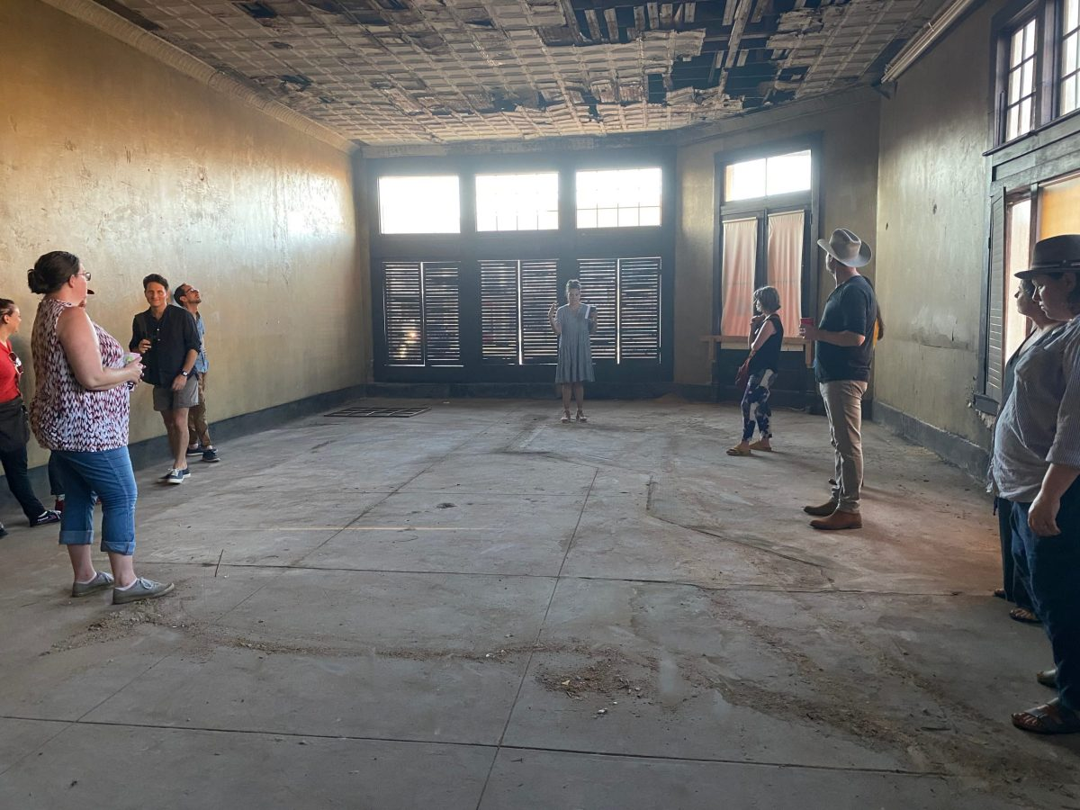Curator Leslie Moody Castro demonstrates that the Williamson and Bell County Line runs through a former tavern in downtown Bartlett, marked by inset floor tile.