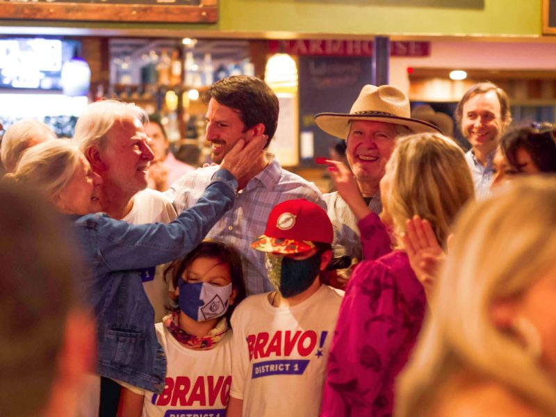 Mario Bravo (D1), center, smiles with supporters during his watchparty at Backyard on Broadway on Saturday. He overcame his opponent Reoberto Treviño in the June runoff election.