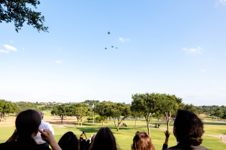 Family and friends of the late James Calvert gather outside of the San Antonio Country Club to watch the missing man formation flyover honoring the WWII veteran.