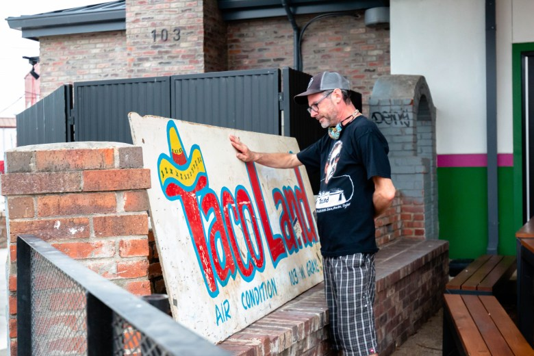 """Patrick Smith tears up while touching the original Taco Land sign after the dedication ceremony honoring """"Ram"""" Ayala's life. Smith said that he knew Ayala and used to take photos and videos at some of the shows at Taco Land back in the early nineties."""