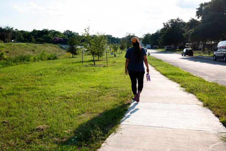 Laura walks along a drainage area that used to have a row of mid-centurty homes that had to be removed to make room for proper drainage in the Ridgeview neighborhood.
