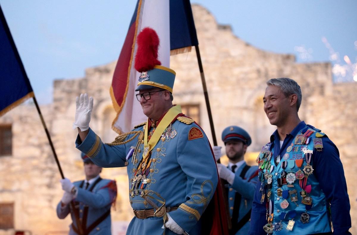 King Antonio XCVIII Phillip Peacock Bakke waves to the crowd alongside Mayor Ron Nirenberg after his investiture at Alamo Plaza on Saturday.