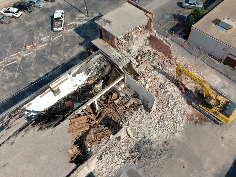Crews started to demolish a portion of the Whitt Printing Company building in the Cattleman Square Historic District on Thursday.