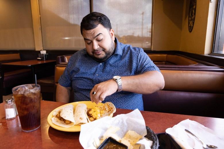 Serna enjoys his regular order of two papa and chorizo tacos and one ham taco at the Las Palapas on Blanco Road Friday.