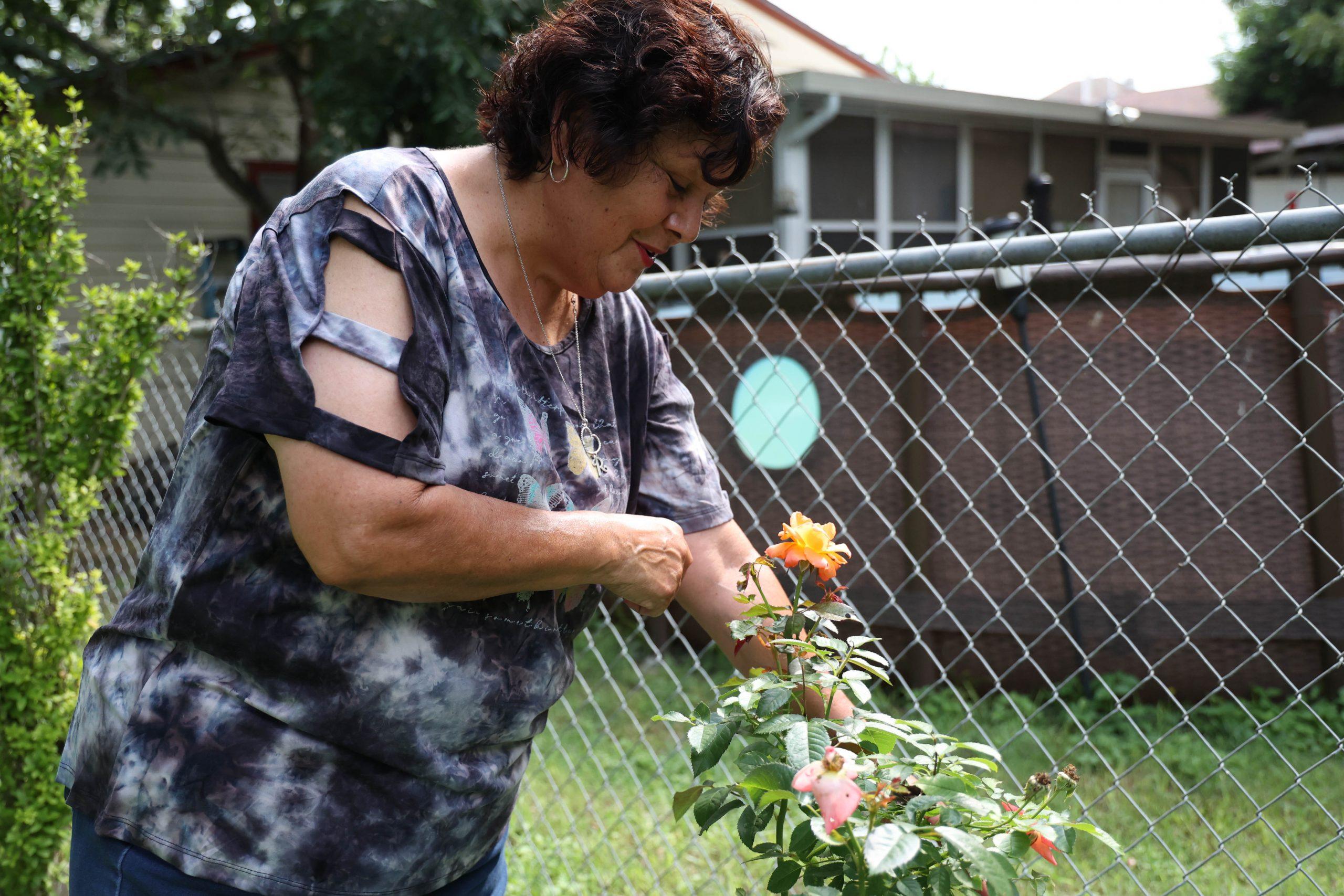 Baca admires a flower growing in her garden.