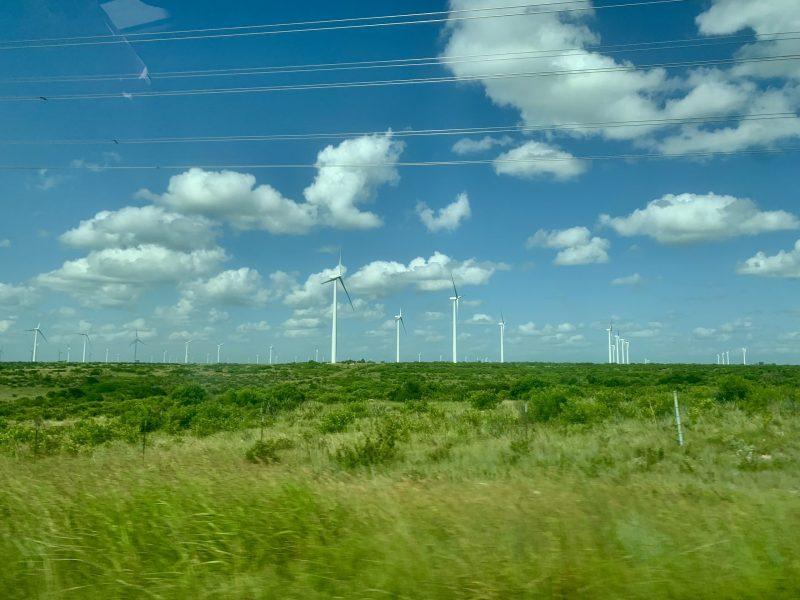 Wind turbines stand in an open field in West Texas.