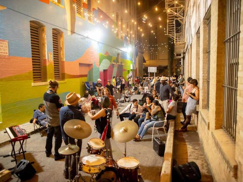A band plays live music in Peacock Alley while the audience listens and mingles during a Friyay event hosted by Centro.