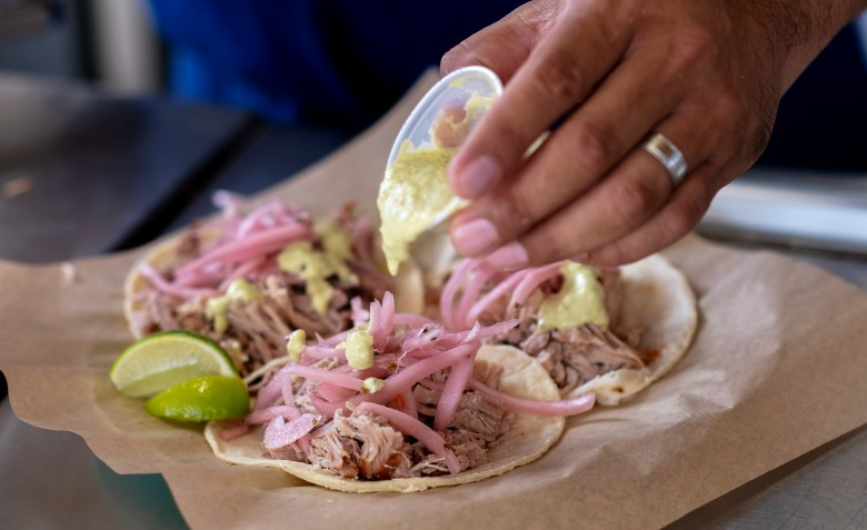 Carnitas Lonja chef Alex Paredes adds salsa to a carnitas taco on Wednesday.