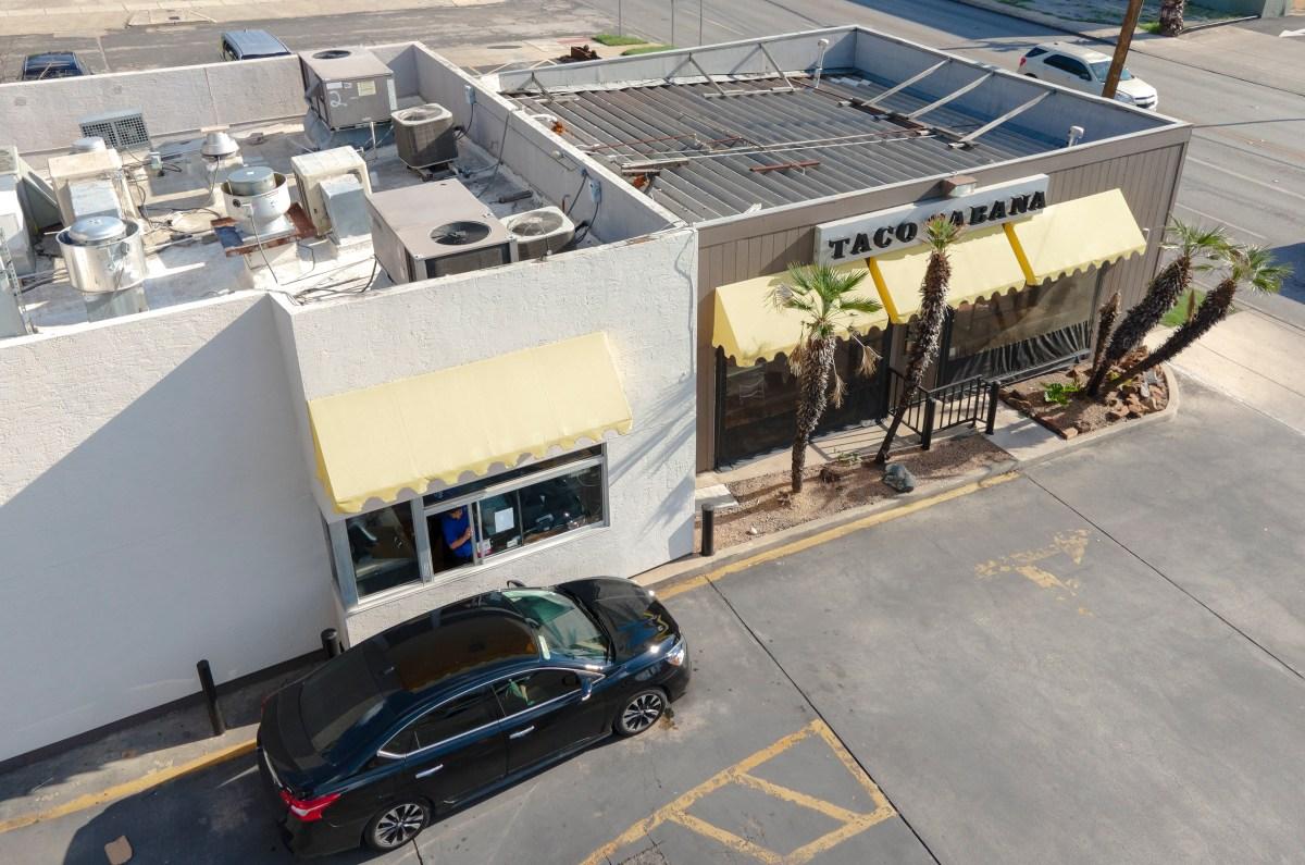 A Taco Cabana employee serves a customer at the drive thru window at the company's original location on Thursday.