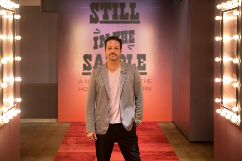 """Jason Kirkland, exhibition manager at the Briscoe Western Art Museum, stands in front of the """"Still in the Saddle"""" exhibit on Tuesday."""