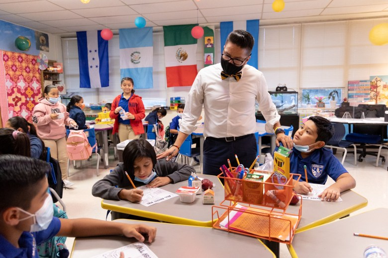 Fifth-grade bilingual teacher Miguel Rodriguez checks on students work on the first day of school at Democracy Prep.