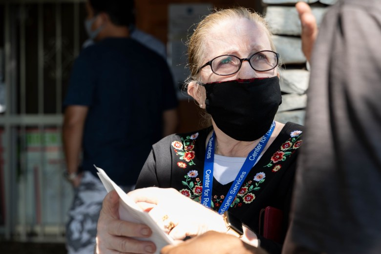 Margaret Constantino, executive director of the Center for Refugee Services, explains how to fill out a form to a man seeking assistance on behalf of his family members still trying to escape Afghanistan Thursday.