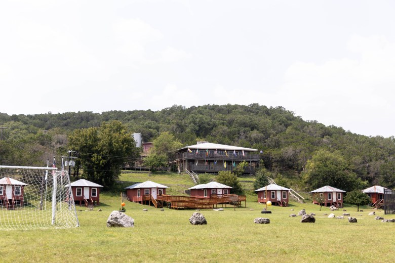 The mess hall overlooks a row of small cabins in front of the soccer pitch at Camp Flaming Arrow.