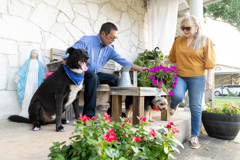 Velma Peña and her husband Tony enjoy the flowers on their front porch with their two dogs Texan and Archie.
