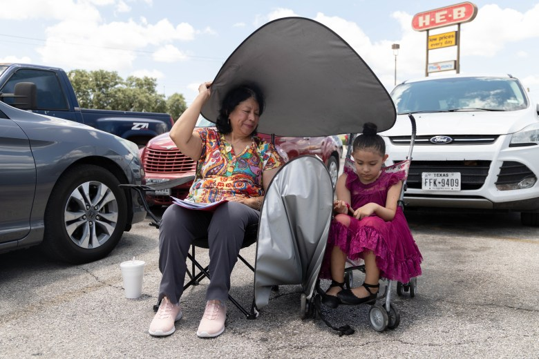 Maria Valdez sits in the parking lot outside of Councilwoman Castillo's (D5) field office with her granddaughter Bea Gonzales, awaiting further assistance with her utility payments.