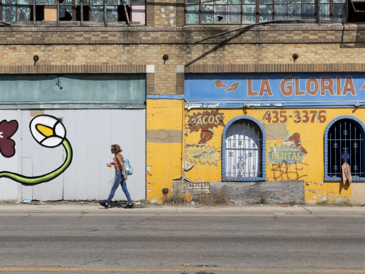 A pedestrian walks along the Basila Frocks Building where Albert Gonzales installed a wabi sabi flower on Thursday.