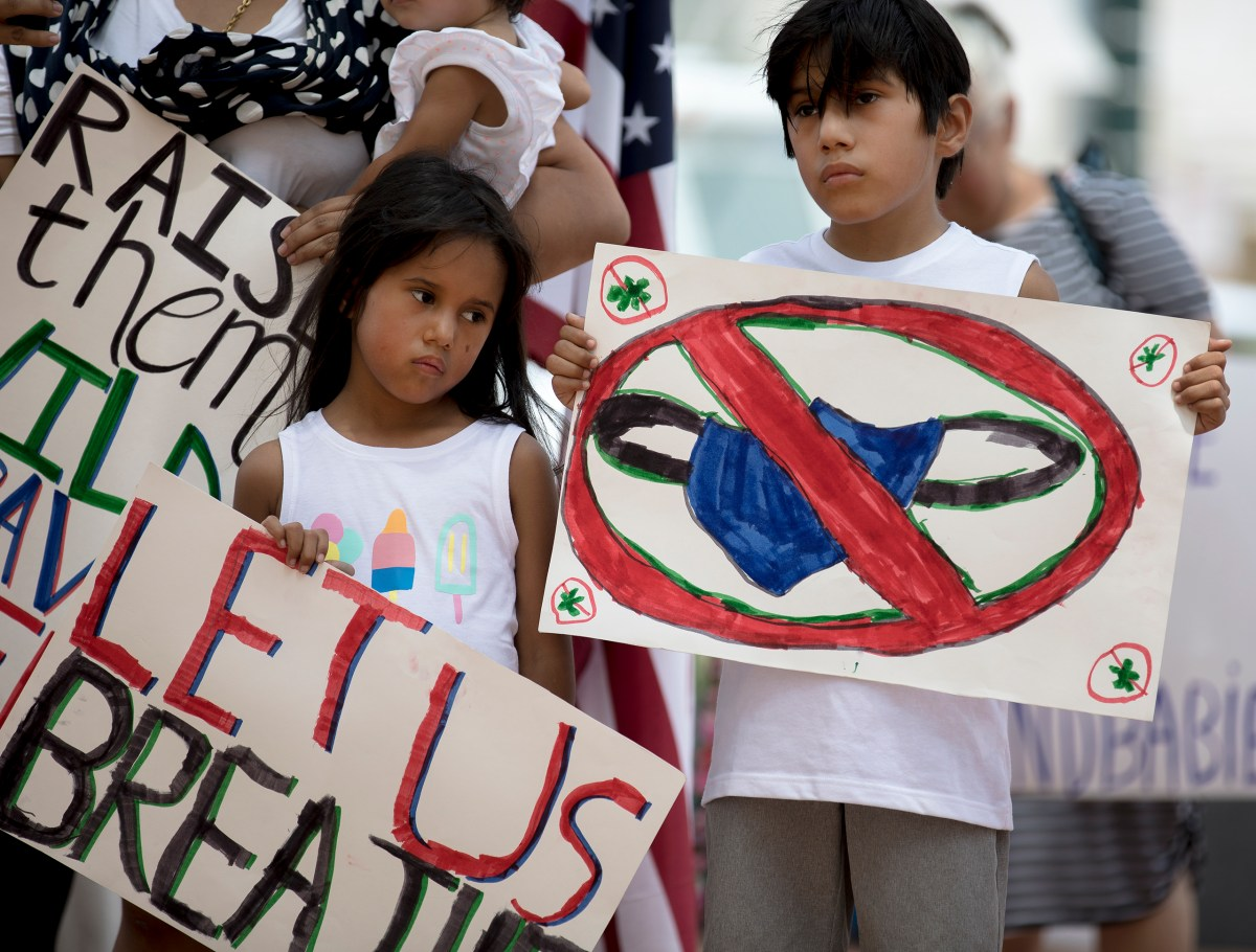 Laila Hernandez and her brother, Kai, hold signs during a protest against wearing masks on Friday.