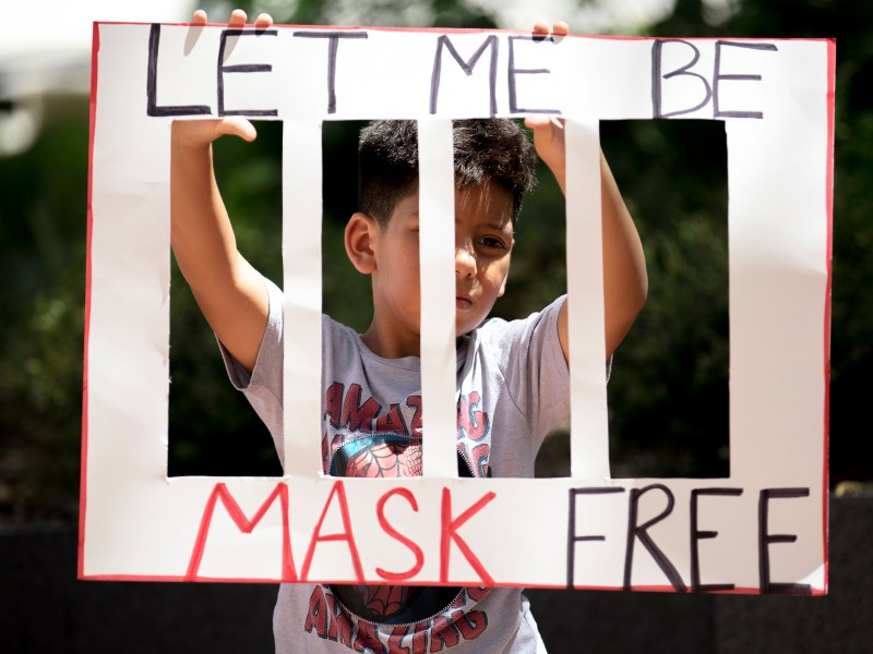Joel Anzures holds up a sign during a protest against wearing masks on Friday.