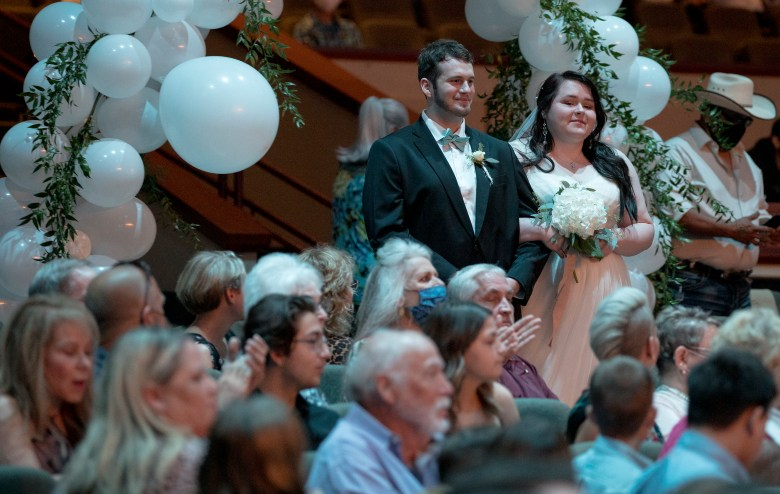 Nellie Hazard and Stephen Mendenhall walk down the aisle during a mass wedding ceremony at Community Bible Church on Saturday.