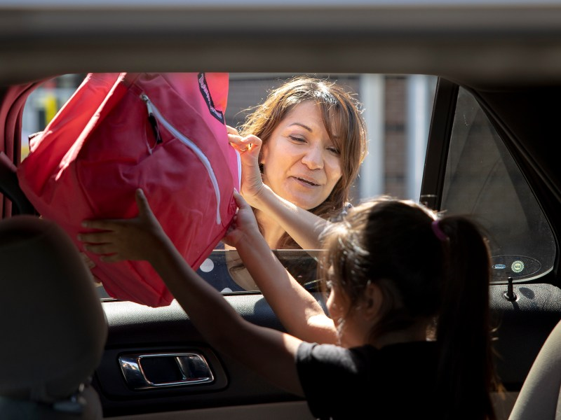 City Council member Melissa Cabello Havrda (D6) hands a backpack full of school supplies to first grader Anjali Perez at the Edgewood Theater of Performing Arts during a back to school distribution event on Saturday.