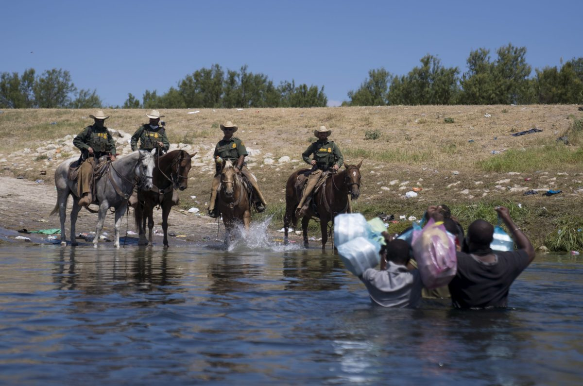 U.S. Border Patrol agents stop migrants crossing the Rio Grande River near the Del Rio-Acuna Port of Entry in Del Rio, Texas, U.S., on Sunday, Sept. 19, 2021. U.S. officials plan to expel thousands of Haitian migrants that arrived at the small Texas city of Del Rio this week.