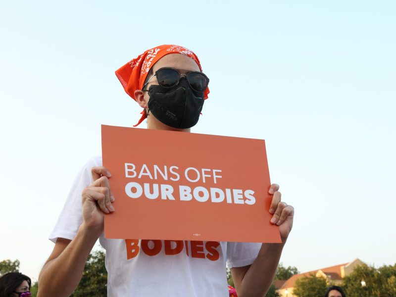 """A protester holds a sign that reads """"Bans Off Our Bodies"""" last week at San Pedro Springs Park during a statewide protest against Texas' new abortion ban."""