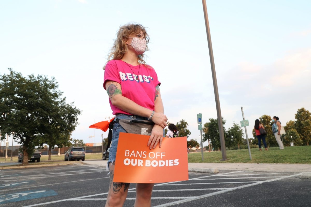 """Hannah Taylor, a volunteer with Planned Parenthood holds a sign that reads """"Bans Off Our Bodies"""" at the statewide protest against the Texas's six-week abortion ban in San Pedro Springs Park Wednesday."""