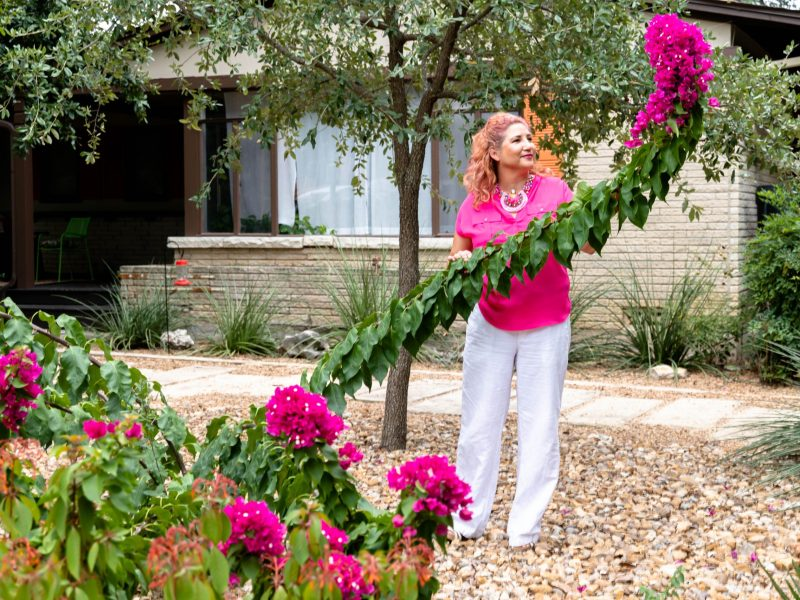 Rodriguez Brigant admires one of the plants in her garden Wednesday.
