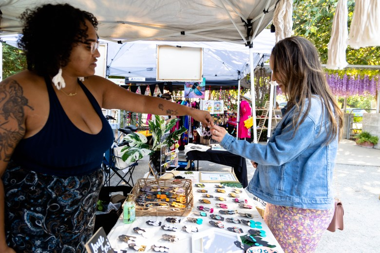 Herrara purchases handmade clay earrings from BriAnna Martinez-Brooks at the pop-up market in front of Elsewhere Garden Bar and Kitchen Thursday.