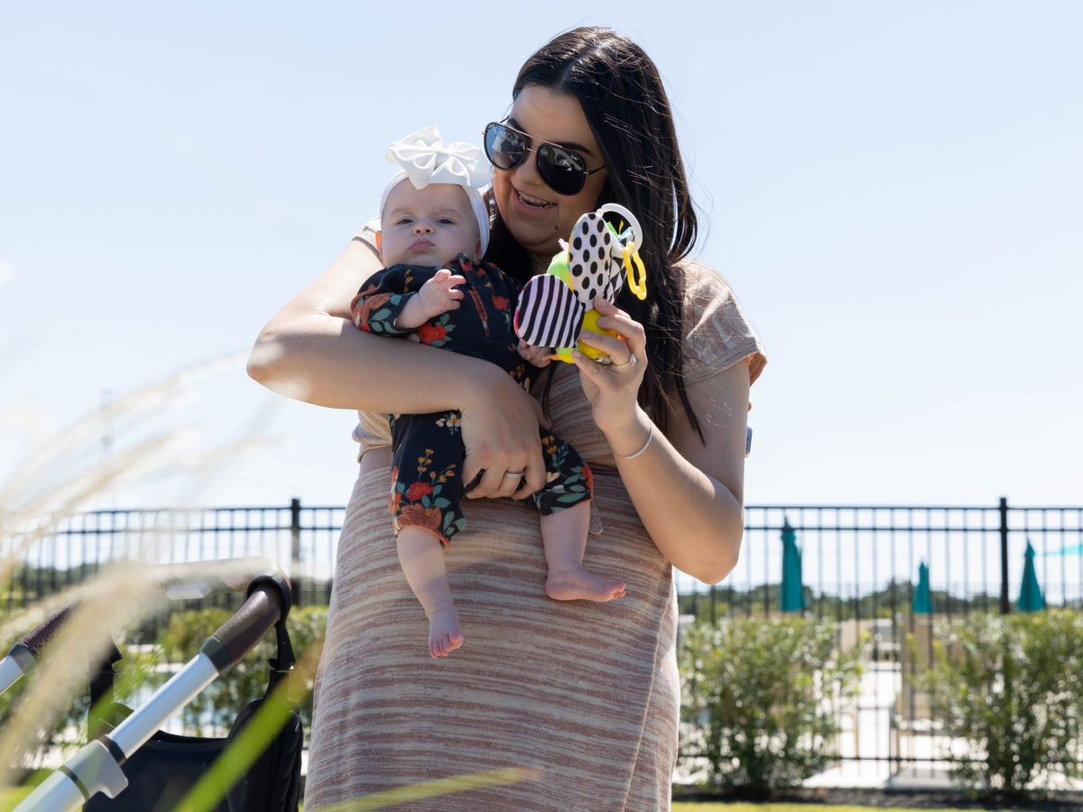 Garza plays with her newborn daughter, Emerson, near the community pool and amenity center in her new neighborhood Friday.