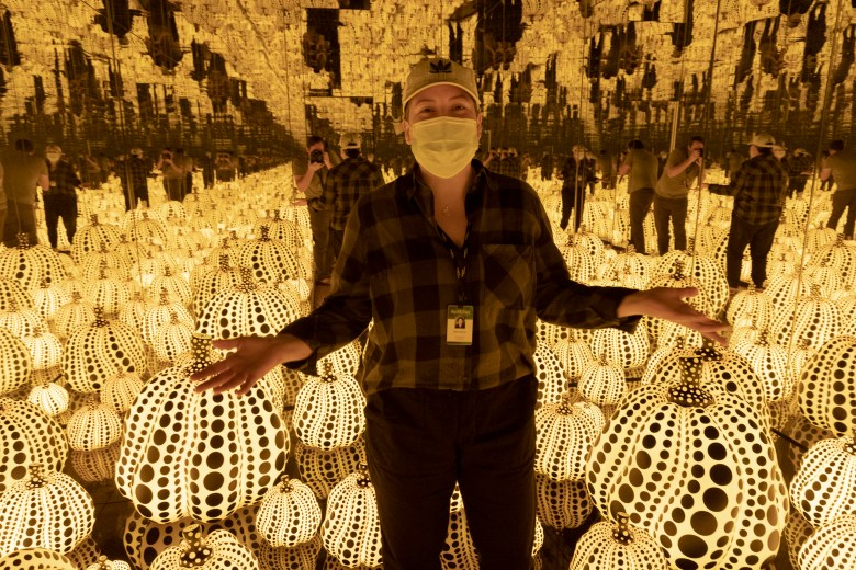 Cherise 'Rhys' Munro stands inside Yayoi Kusama's <i>All the Eternal Love I Have for the Pumpkins</i>.