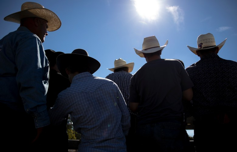 Men gather around a bull riding chute at the rodeo during the Comal County Fair in New Braunfels on Sunday.