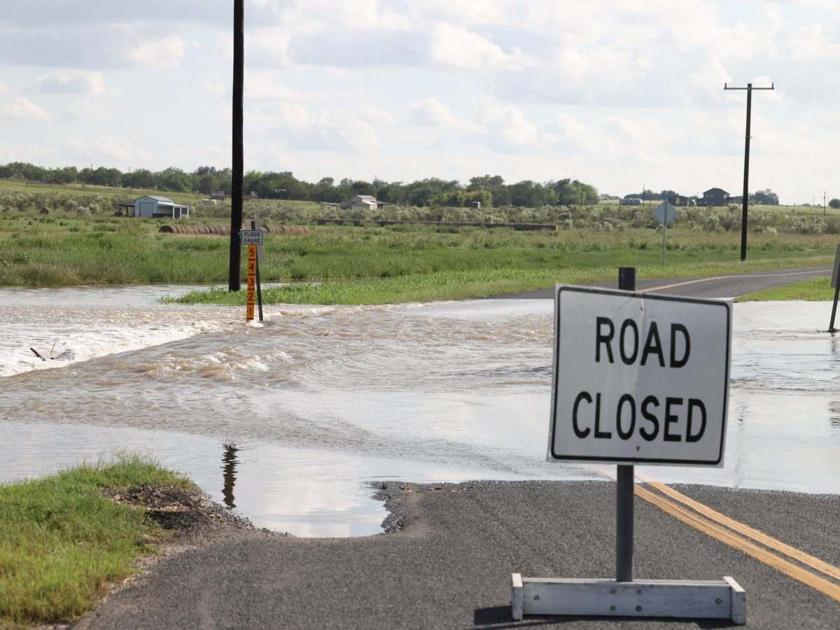 Floodwaters rush across Abbott Road in St. Hedwig Thursday.