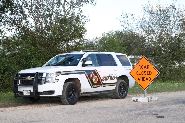 A Bexar County Sheriff's deputy drives past a barricade closing off part of North Graytown Road in St. Hedwig, where crews have been working to locate a missing girl and woman who were swept away in floodwaters Thursday.