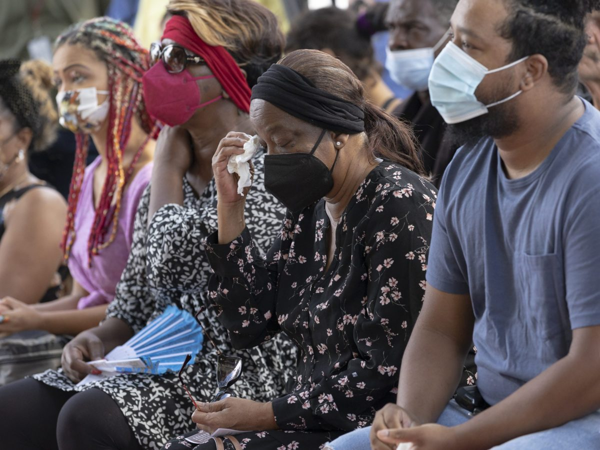 Margaret Hawkins, the mother of William Hawkins wipes her eyes with a tissue during the memorial to her son who was shot and killed.