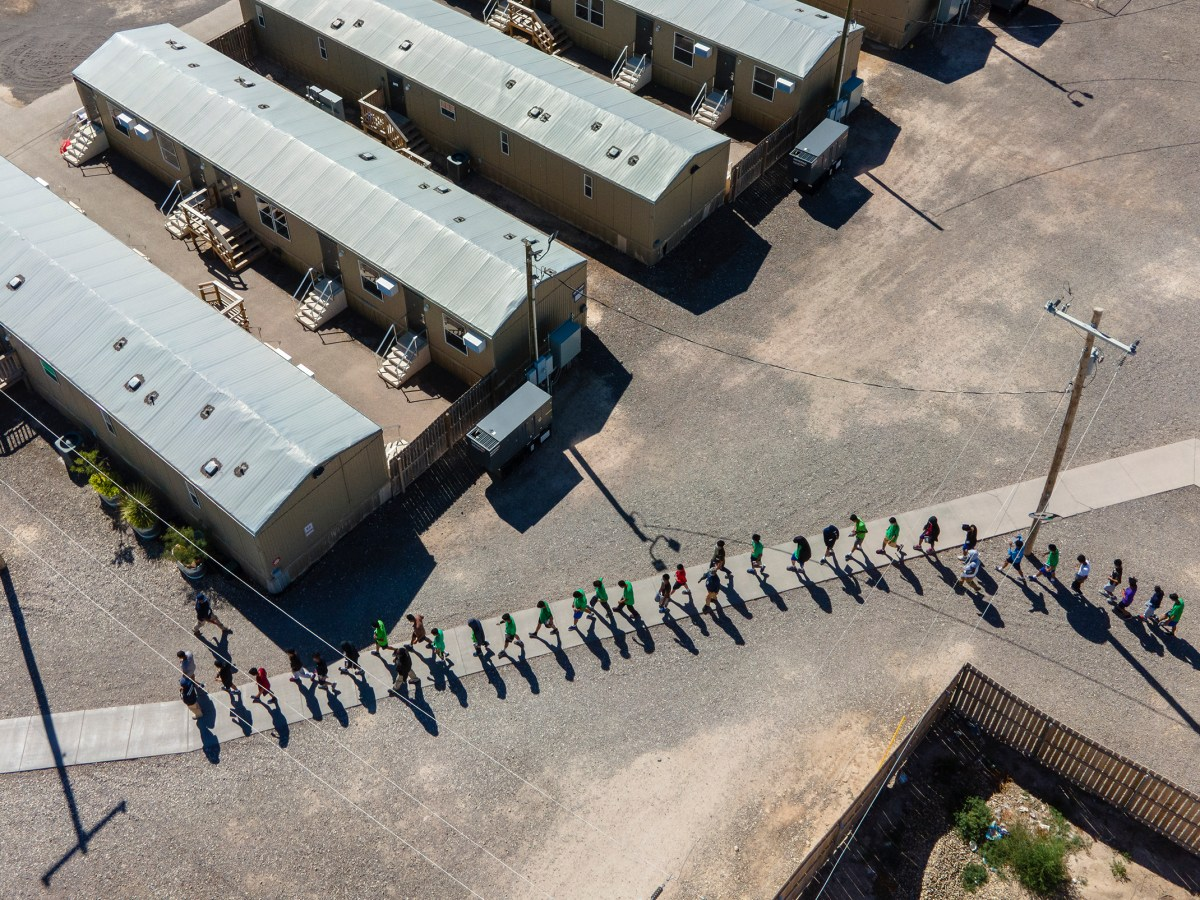 Endeavors employees escort a line of teenage boys at a migrant youth detention center in Pecos on Tuesday.