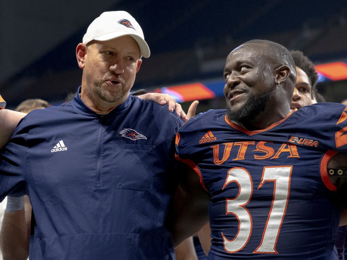 UTSA coach Jeff Traylor, who could potentially leave the undefeated team for a position at Texas Tech, sings the school song with linebacker Nate Hawkins (37) following their 45-0 win against Rice University.